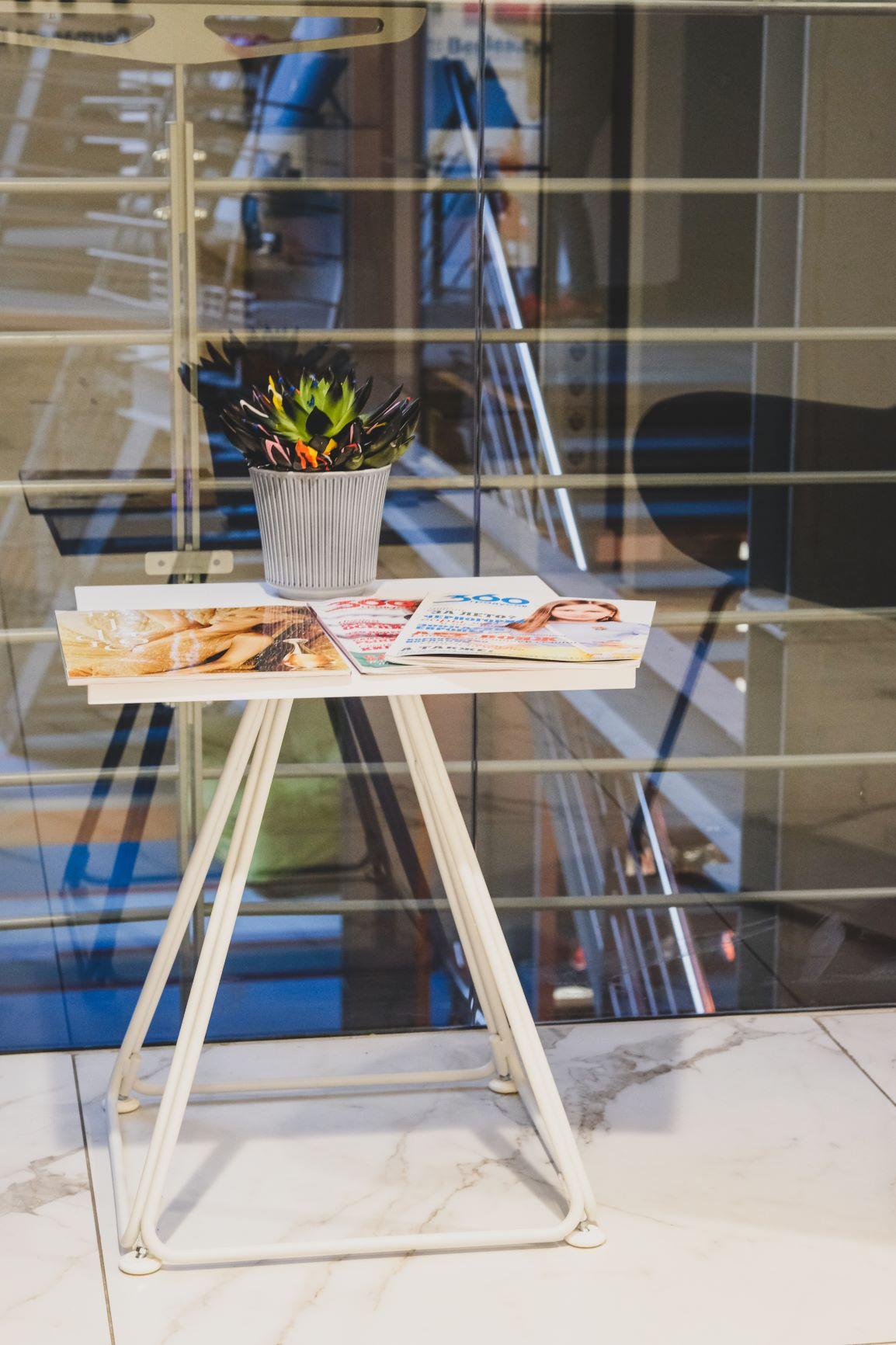 Elegants kafijas galdiņš ar baltām metāla kājām un kantainu virsmu