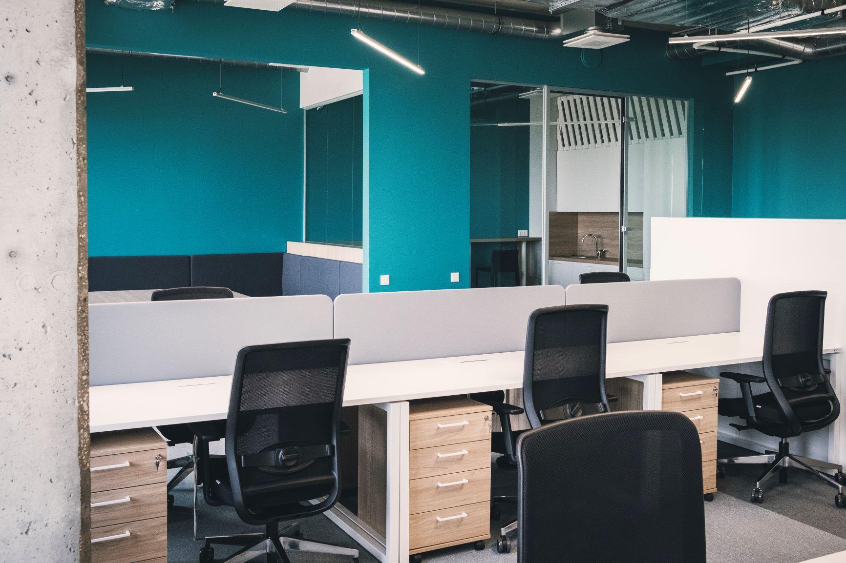 Darba vietas ar ergonomiskiem Luxy krēsliem un biroja galdiem ar baltu virsmu un ietilpīgiem atvilktņu blokiem